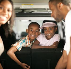 A happy family  with their minivan.