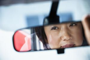 bigstock-Woman-Looking-in-Rearview-Mirr-7629395